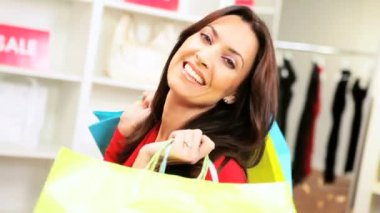 Brunette Caucasian female close up displaying designer bags successful shopping trip