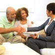 Senior Ethnic Couple Meeting Saleswoman Home - Stock Photo
