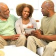 Ethnic Son and Senior Parents Using Wireless Tablet - Stock Photo