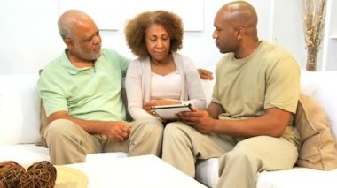 Adult African American son showing elderly parents his wireless tablet