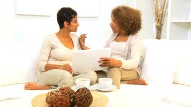 Senior African American mother and daughter using laptop home sofa