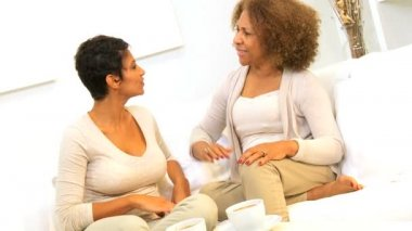 African American mother and daughter enjoying quiet time together drinking coffee