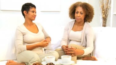 Ethnic mother and daughter enjoying quiet time together drinking coffee