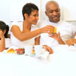 Stock Video: Young Ethnic Family Breakfast Bed