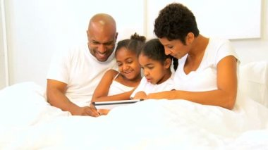 African American couple relaxing bed young daughters wireless tablet