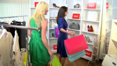 Caucasian girlfriends shopping together in chic designer boutique