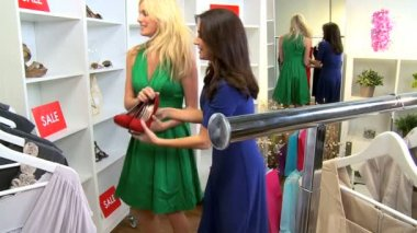 Girlfriends looking at new shoes in exclusive boutique