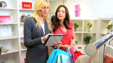 Brunette customer being shown online fashion collection wireless tablet by boutique assistant