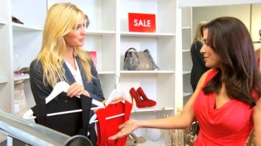 Brunette female shopper helped by young owner in designer boutique