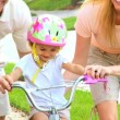 Young Parents Supporting Toddler on Little Bicycle - Stock Photo