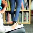 Royalty-Free Stock Векторное изображение: Female student listening to mp3 player in college hub