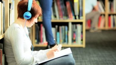 Caucasian female student study and listening to mp3 player in campus library