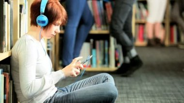 Female Caucasian classmate using tablet and listening IT lecture in college library