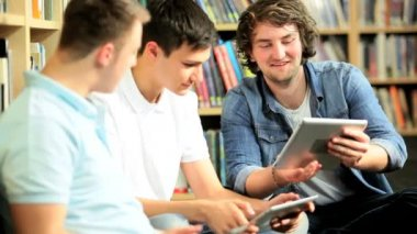Indian and Caucasian students networking on tablets — Stock Video
