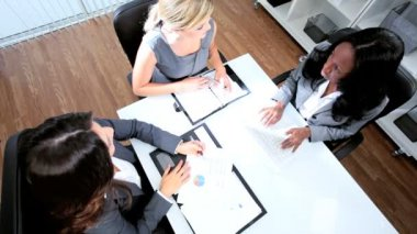 Group of Caucasian and African American management female focusing on future benefits with laptop in modern office overhead shot