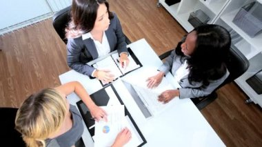Manager conference of diverse business women agreeing strategy with handshake in modern boardroom overhead shot