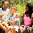 Ethnic mother and father relaxing with children — Stock Video