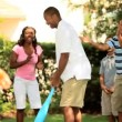 Happy children encouraging their parents playing baseball — Video