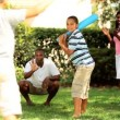 Vídeo Stock: Diverse happy family playing baseball on vacation