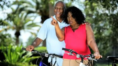 Ethnic senior couple keeping fit on bicycles — Stock Video