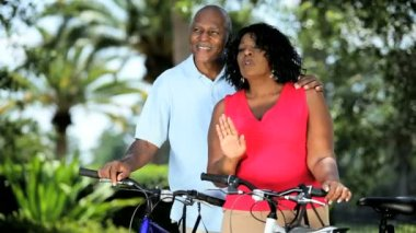 Diverse couple keeping fit and healthy cycling — Stock Video