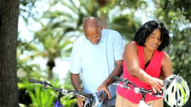 Mature diverse couple getting ready for cycling — Stock Video