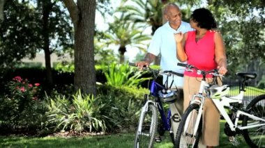 Mature ethnic couple keeping fit in retirement on bicycles — Stock Video