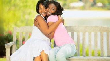 Loving African American mother daughter spending time together sitting garden bench 