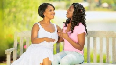 African American young daughter and affectionate mother have fun on park bench