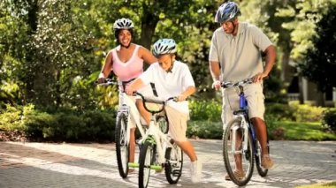 Healthy diverse family bike riding together in park — Stock Video