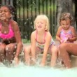 Multi ethnic girls splashing each other in swimming pool - Stock Photo