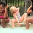 Stock Video: Multi ethnic children laughing and splashing in swimming pool