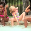 Multi ethnic children laughing and splashing in swimming pool — Stock Video