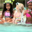 Diverse children playing water in swimming pool on holiday — Stockvideo
