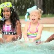 Stock Video: Diverse girls splashing each other in outdoor pool