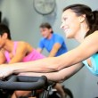 Gym Members Riding Exercise Bicycle - Stock Photo