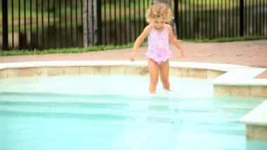 Little blond Caucasian girl enjoying swimming pool in home garden