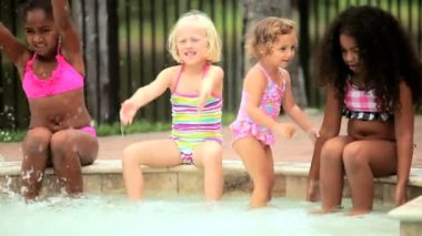 Cute little multi ethnic friends on holiday playing together outdoor swimming pool