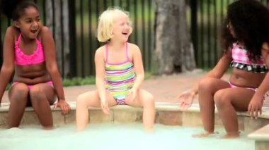 Little Caucasian African American happy girls enjoying healthy outdoor activity in water swimming pool