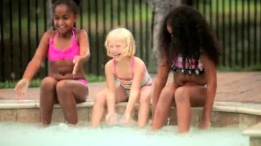 Multi ethnic little happy children enjoying sunshine together in outdoor swimming pool