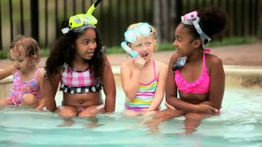 Caucasian and African American little lucky girls sitting in snorkel together in swimming pool