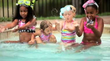 Pretty toddler multi ethnic girls on vacation playing in outdoor swimming pool