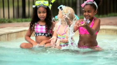 Healthy young multi ethnic happy children playing water in outdoor swimming pool on holiday