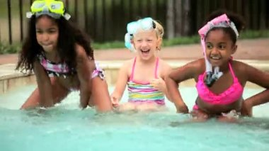 Cute Caucasian African American children enjoying healthy activity in water swimming pool