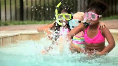 Multi ethnic children in masks splashing in swimming pool — Stock Video