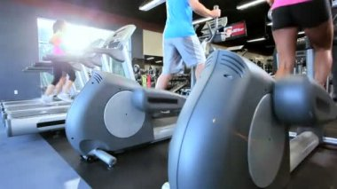 Gym members exercising on modern cross trainer and treadmill equipment