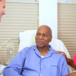 Doctor Treating Senior Male Patient - Stock Photo
