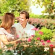 Young Couple Enjoying Garden in Summer - Stock Photo