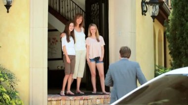 Young Caucasian wife teenage daughters greeting father on return from work
