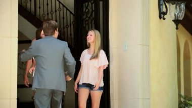 Caucasian father returning from business trip being greeted by wife teenage daughters